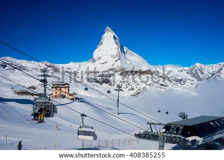 Zermatt, Switzerland- April 14,2016 : unidentified ski players sit in ski lift with Matterhorn Peak background - stock photo