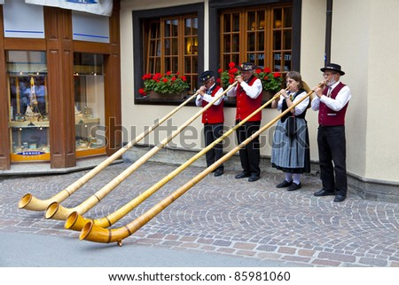 ZERMATT, SWITZERLAND - AUGUST 14: Swiss musicians play in Zermatt streets on August 14, 2011 during the 2011 Folklore Summer Festival where more than 50 groups and 1200 Swiss dancers took part. - stock photo