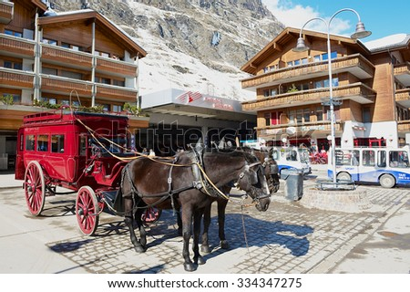 ZERMATT, SWITZERLAND - MARCH 03, 2009: View to the horse carriage waiting for passengers in front of the Zermatt railway station in Zermatt, Switzerland. - stock photo