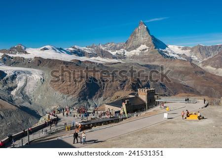 ZERMATT, SWITZERLAND- SEPT 29, 2009: Tourists at Gornergrat viewpoint  with Matterhorn peak in the background. It is one of the most tourist attraction in Switzerland. - stock photo