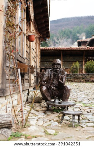 Zheravna, Bulgaria ? Mart 13, 2016: Bronze sculpture, statue of a man sitting on a chair near to a small table and drinking coffee. Street with cobble stones of museum Zheravna village in Bulgaria - stock photo