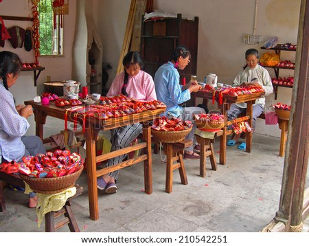 ZHOUZHUANG, SHANGHAI-SEPTEMBER 25, 2005: local ladies working in a shoes factory.  Zhouzhuang water village is Shanghai tourist attraction with 1000000 visitors year - stock photo