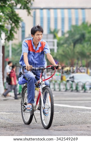 ZHUHAI-CHINA-SEPTEMBER 5, 2013. Young worker on his bicycle in the city center. Article 15 of the (PRC) Chinese Labor Law (1994) prohibits the employment of persons under the age of 16 years. - stock photo