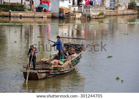 ZHUJIAJIAO, CHINA - NOVEMBER 10, 2014:  Local fishing people navigate boat in the ancient water town of Zhujiajiao located in the Qingpu District of Shanghai. - stock photo