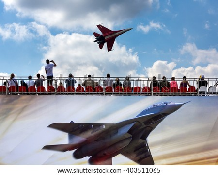 """ZHUKOVSKY, MOSCOW - AUG 16: Spectators in the stands and Russian fighter aircraft MIG-29 at """"AirShow Furious 2014"""" on August 16, 2014 in Zhukovsky, Moscow region, Russia - stock photo"""