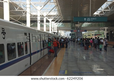 ZHUZHOU - HUNAN, CHINA - OCTOBER 3: Passengers enter train to Guangzhou on October 3, 2010 in ZhuZhou station.China invests in fast and modern railway, trains with speed over 340 km/h. - stock photo