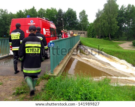 ZIELONA, POLAND - JUNE 11: A man from fire department to protect the causeway between the upper and lower pond in the Zielona in 11 June 2013 Kalety. High water levels in Zielona and river Mala Panew.