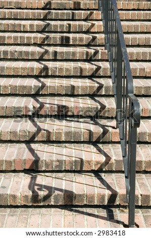 Zigzag shadows of black handrail on red brick stairway on college campus
