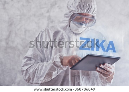 Zika virus concept, medical worker in protective clothes using digital tablet computer to access internet and study symptoms, diagnosis and treatment of this illness. - stock photo