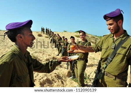 ZIKIM - SEPTEMBER 07:IDF soldiers are blessing on the traditional Jewish custom of apple and honey to welcome Rosh Hasahanah, the Jewish New Year on September 07 2010 in Gaza border near Zikim, Israel