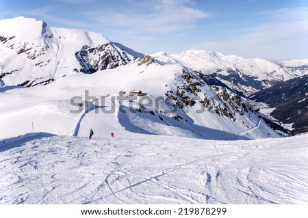 Zillertal Alps in Austria, ski piste, hut and Tuxtal valley viewed from the summit of Tuxkogel mountain at sunset light in winter - stock photo