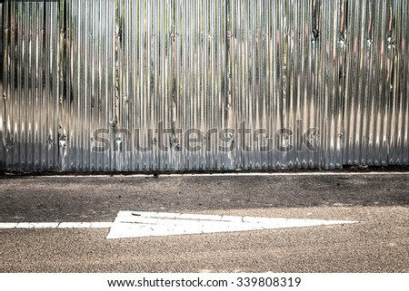 zinc fence with white arrow on  background - stock photo
