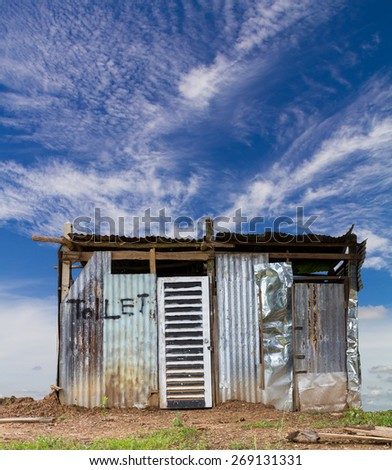Zinc old toilets on the ground in the field, cloudy sky as a backdrop. - stock photo