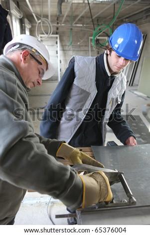 Zinc worker and apprentice - stock photo