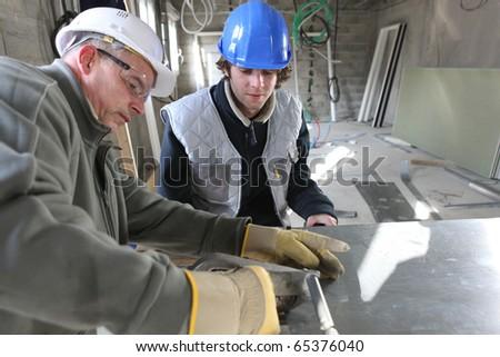 Zinc worker and apprentice in workshop - stock photo