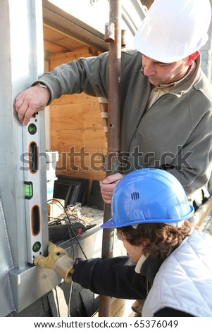 Zinc worker and apprentice laying zinc