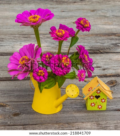Zinnia flowers in a decorative watering can and birdhouse on a wooden table