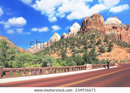 Zion National Park USA. Excellent with red asphalt road among the picturesque mountains of orange and red sandstone. Photographer in a black T-shirt and black jeans pictures of the spectacular scenery - stock photo
