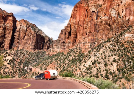 Zion National Park, Utah. Red vintage trailer going down the road. Majestic mountain scenery.  - stock photo
