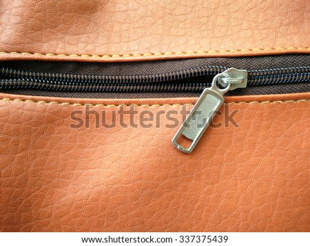 zippers on brown leather.