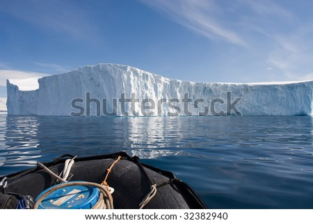 zodiac stopped by a wall of ice - stock photo