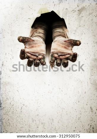 Zombie hand through cracked wall - stock photo