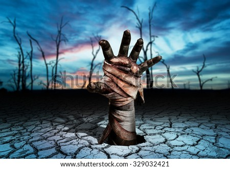 Zombie hand through Soil cracked in Magic land and blurred tree die background.Halloween theme