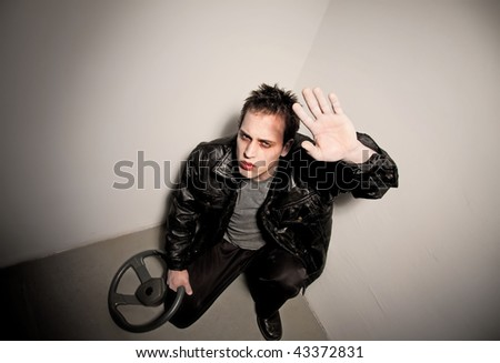 Zombie hiding in a corner holding car steering wheel - stock photo
