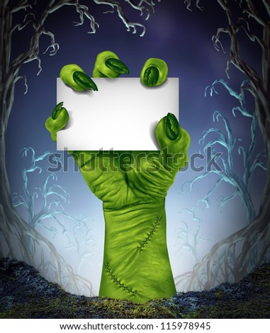 Zombie rising hand holding a blank sign card as a spooky halloween or scary symbol with textured green monster skin in a foggy night tree forest background as a cemetery like creepy place. - stock photo