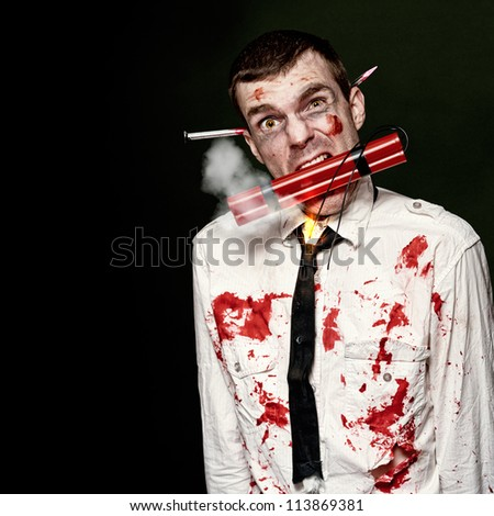 Zombie Suicide Bomber Holding A Mouthful Of Dynamite While Initiating A Halloween Zombie Apocalypse On Dark Studio Background - stock photo