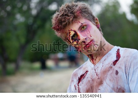 Zombie teen outside with yellow eyes looking at camera - stock photo