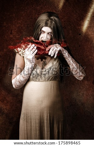 Zombie vampire woman eating human hand in splashes of bloody horror - stock photo