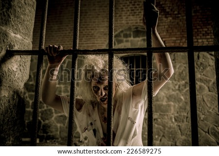 Zombie woman at the window - stock photo