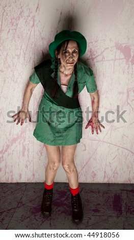 Zombie woman in scout clothing covered in blood - stock photo