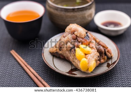 Zongzi or Asian Chinese sticky rice dumplings with Yellow tea, soup, sauce and chopsticks on dark table surface. Zongzi is a traditional Chinese food eaten during the dragon boat festival. / closeup - stock photo