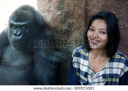 Zoo visitor at the gorilla enclosure. Cheerful girl next to the gorilla cage. Gorilla makes grimaces at beautiful woman behind the glass cage. Gorilla frowns to visit the zoo. Funny visit zoo. - stock photo