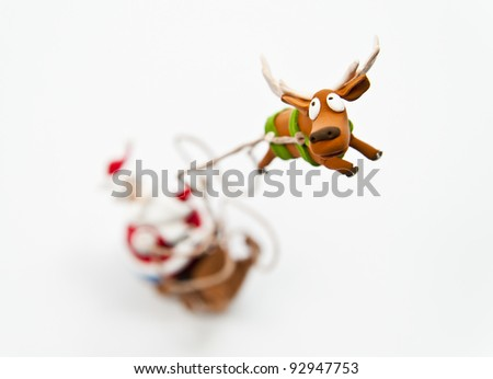 Zoom in reindeer with Santa Claus riding on sleigh - stock photo