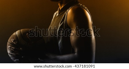 Zoom on a side of a basketball player holding a basketball against a black background - stock photo