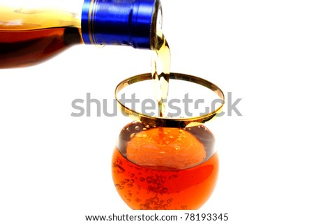 Zoomed bottleneck filling a glass with brown liquid - stock photo