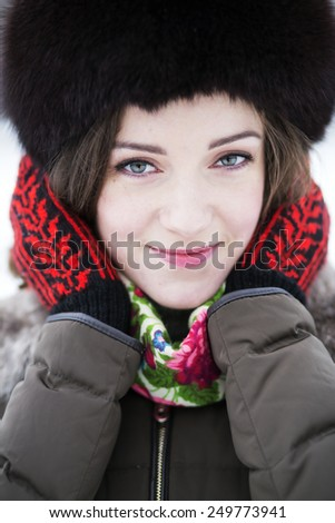 Zoomed portrait of a female in colored mittens - stock photo
