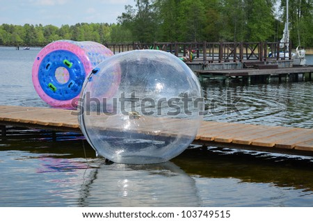 Zorbing air bubbles on water. Marina resort lake in Trakai. Most visited tourist place in Lithuania. - stock photo