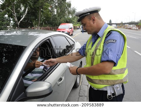 ZRENJANIN, SERBIA - CIRCA AUGUST 2014: Policeman controls drivers at local road, circa August 2014 in Zrenjanin - stock photo