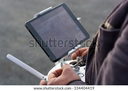 Zrenjanin, SERBIA: October 29, 2015, detail of man flying Dji Inspire 1 remote controller with Ipad displaying camera frame on AVIV park opening - stock photo