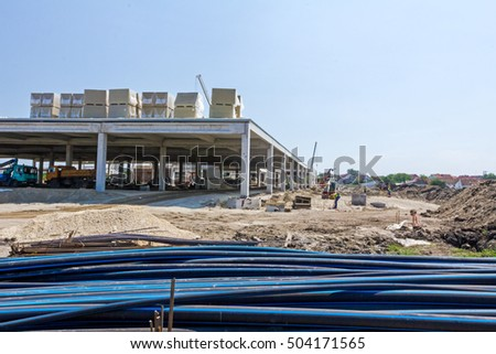 Zrenjanin, Vojvodina, Serbia - June 4, 2015: View on construction site with machinery, people at work. Landscape transform into large urban area, concrete hall.