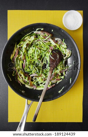 zucchini and bacon in frying pan  - stock photo
