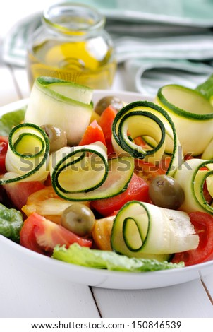 zucchini and tomato salad on white table - stock photo