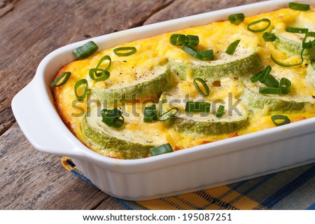 Zucchini baked with cheese, eggs and onion closeup in a white dish. horizontal  - stock photo