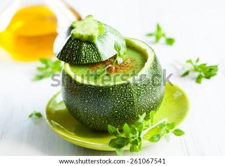 Zucchini cream soup served in a round zucchini. - stock photo