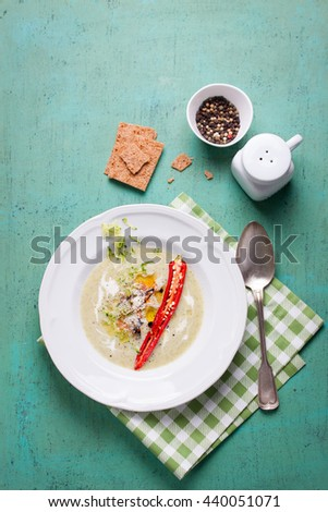 Zucchini cream soup with red pepper, cream, spices and balsamic cream on a wooden background, top view - stock photo