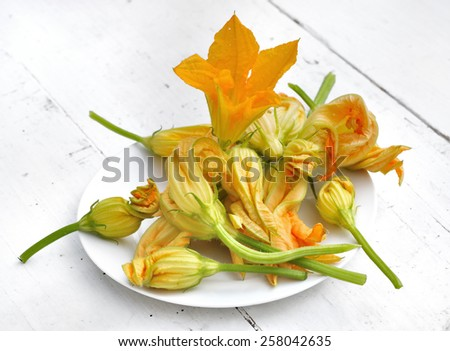 zucchini flowers in a white plate on a table  - stock photo